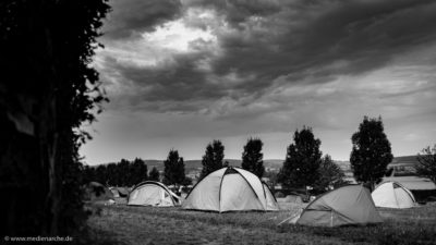 Einige Zelte auf einer Zeltwiese. Im Hintergrund ein aufziehendes Gewitter. Schwarz-weiß Fotografie.