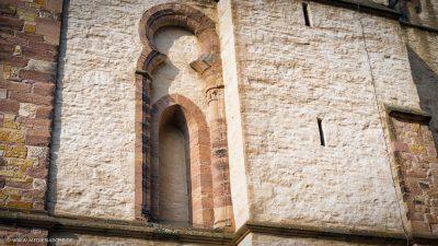 Ein Zierelement an einer Kirchenwand, das ein schmales Fenster andeutet.