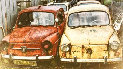 Zwei ausgediente Oldtimer, die auf einem Abstellplatz vor sich hinrosten.