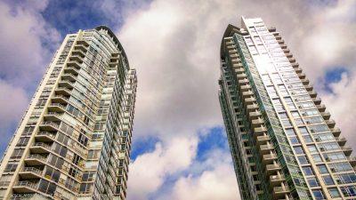 Aufnahme von zwei Wolkenkratzern aus der Froschperspektive. Die Türme sind in sanftes Sonnenlicht getaucht.